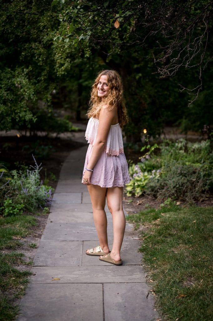 Girl in a pink strapless dress walking away, looking back over her left shoulder.