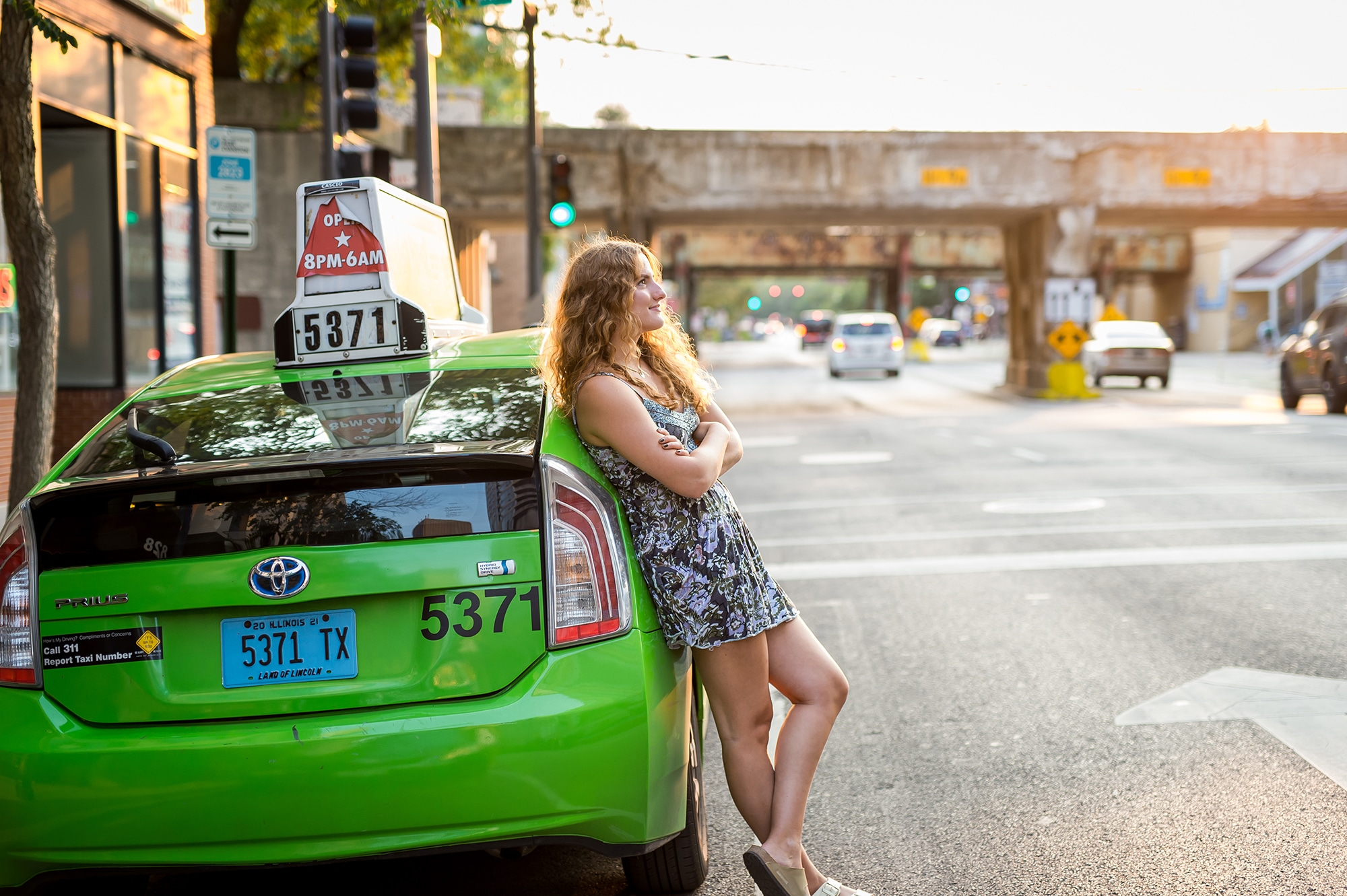 Girl wearing a blue patterned dress leaning on a green taxi cab, with her legs crossed, looking straight ahead. The sun is lighting up her hair.