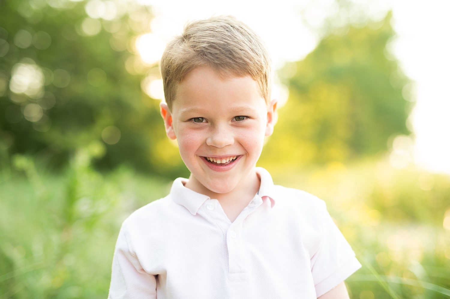 Little boy smiling with grass and trees behind him lit up by the sun.