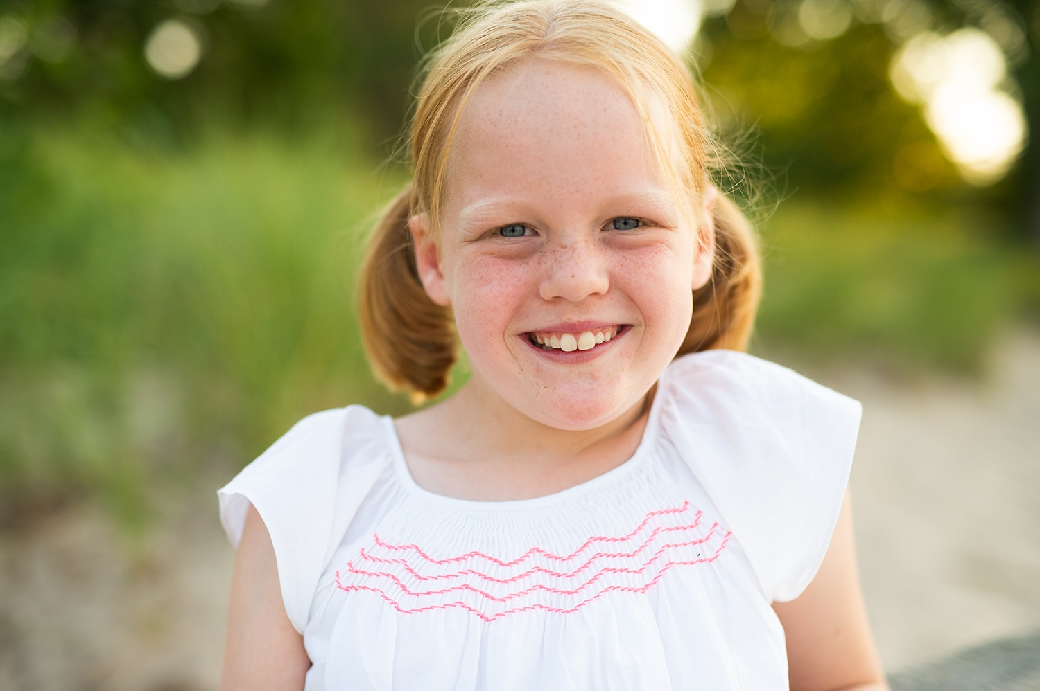 Little girl with red hair and freckles smiling. She's wearing a white dress and her hair is in pigtails.